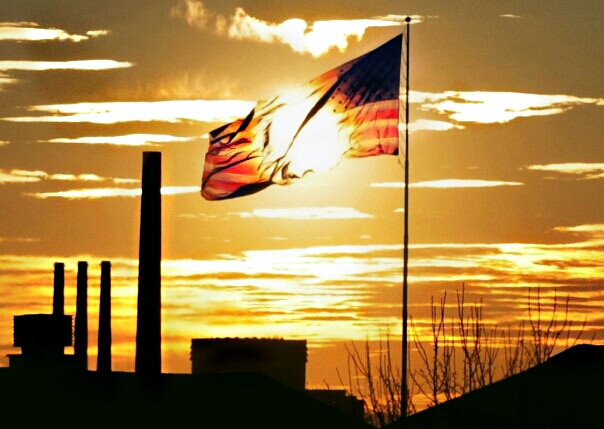 Thank you!!! :) ———————— entry for wapflag. not a political statement...maybe environmental. just thought it was kind of symbolic how it looked like the sun was burning a hole thru the flag, with the factory chimneys as a backdrop. this is one of the views from my bedroom window.